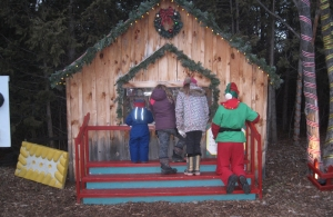 small children and elf look inside small building at christmas village