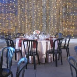 tables in Southlawn tent, back wall covered in strings of lights
