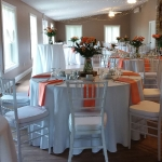 stone house hall interior with tables set and orange napkins
