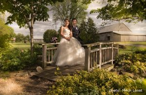 couple on small wooden bridge with barn in background