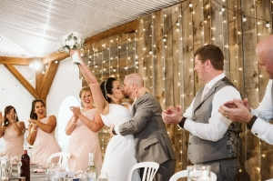 couple kiss at head table inside Southlawn tent
