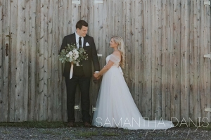 wedding couple in front of barn board