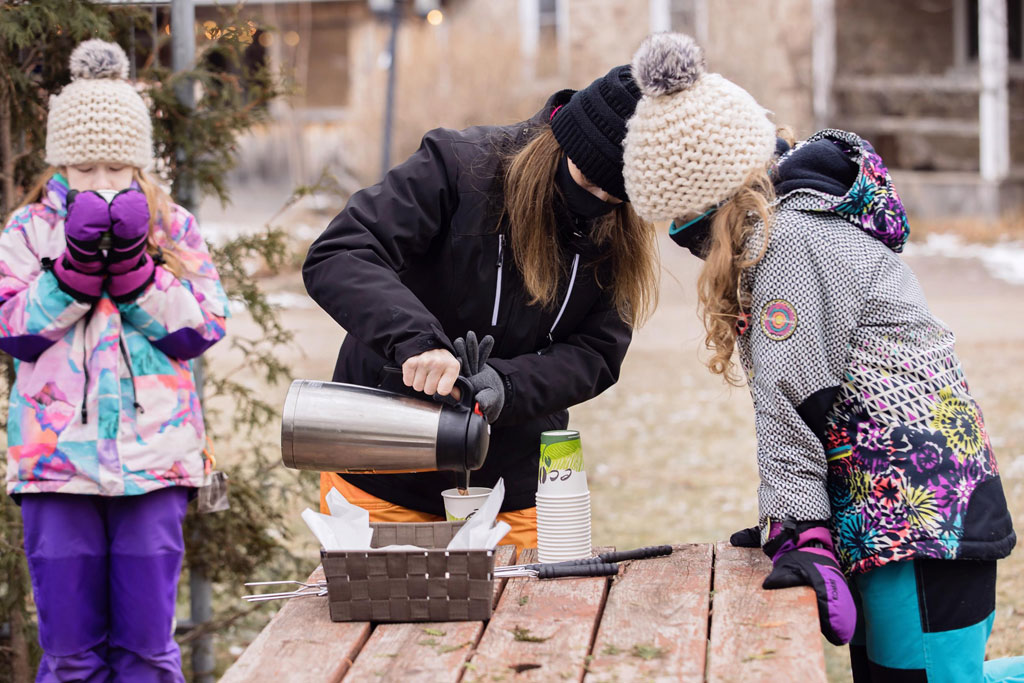 mom pours hot chocolate for children