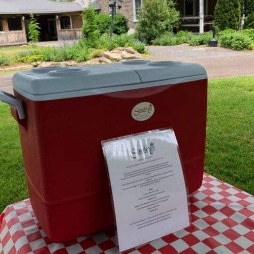 Red picnic cooler in front of old stone house