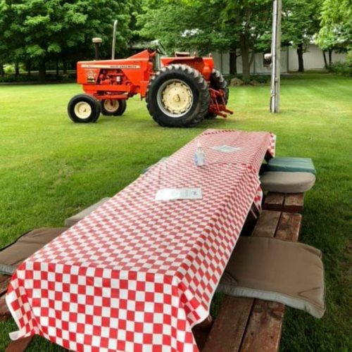 picnic tables with table cloth and red tractor in background